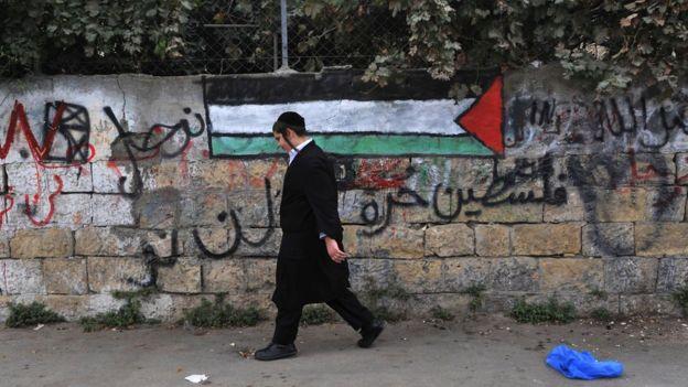 Еврейский ортодокс идет мимо палестинского флага