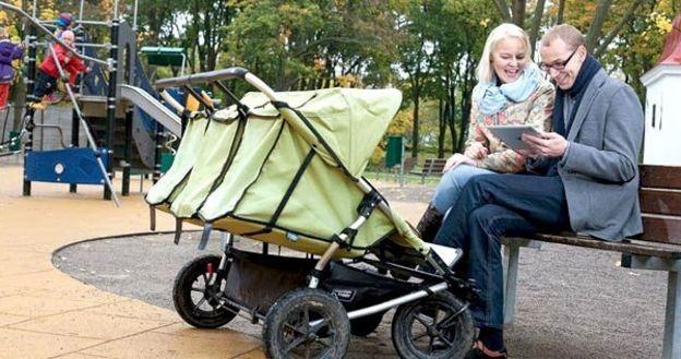 pareja con tableta y carritos de bebé