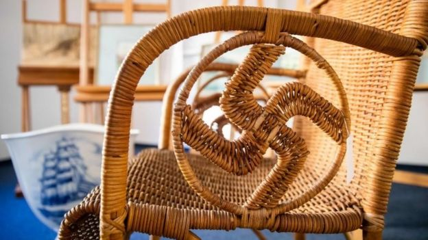 A wicker chair with swastika shape in arms