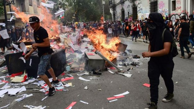 Jóvenes manifestantes prenden fuego a una pila en medio de la calle.