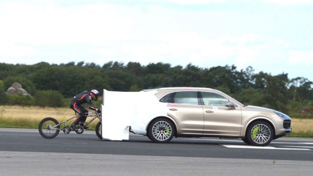 Neil Campbell siendo arrastrado por un Porsche Cayenne