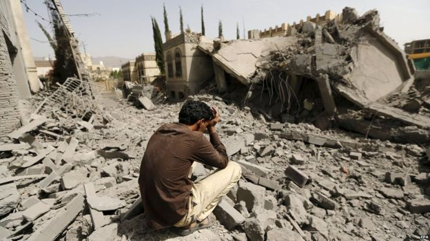 ... A guard sits on the rubble of the house of Brigadier Fouad al-Emad,