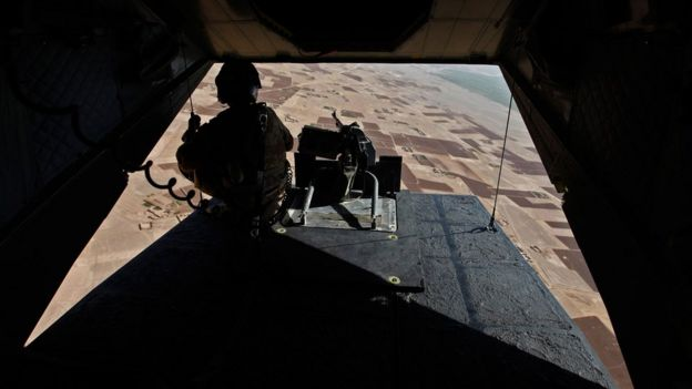 A soldier mans his position at the rear of a British helicopter as it is flown over the Helmand province of Afghanistan on August 31, 2010. (Photo credit should read ANDREW WINNING/AFP/Getty Images)