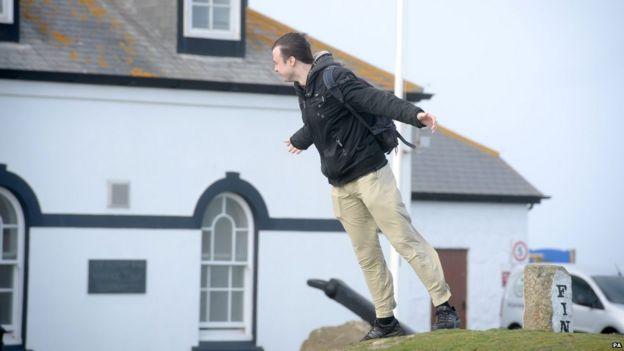 Мужчина пытается устоять на ногах под порывами ветра в Лендс-Энде