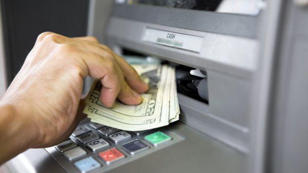 Persona recogiendo dinero de un cajero