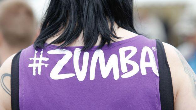 Una mujer lleva una camiseta con el nombre Zumba.