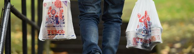 shopper holds a tesco carrier bag in each hand