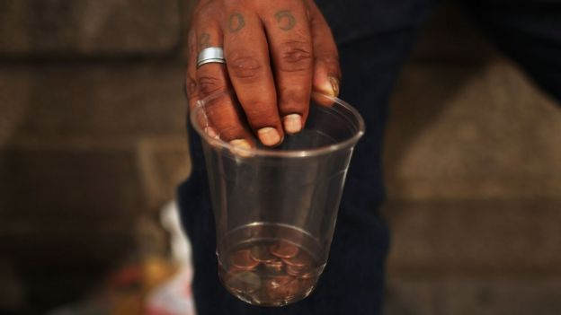 A homeless man holds a cup with coins