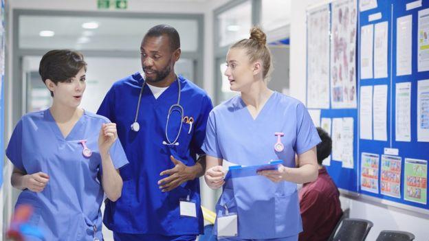 3 nhs nurses walking down corridor