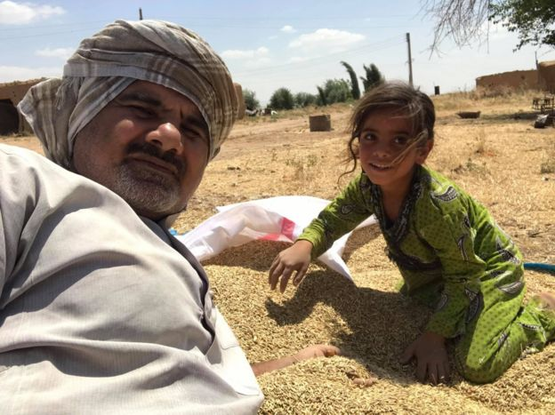 Abood Hamam and a girl with some harvested barley
