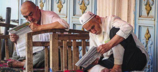 Warga Uighur membaca koran