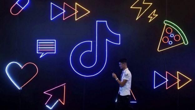 Un joven camina frente a un letrero de TikTok