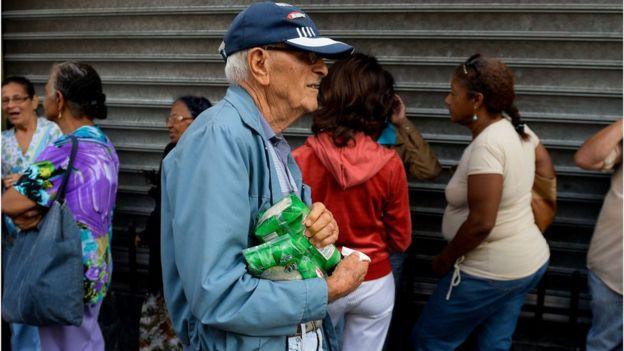 Un hombre pasa con su compra frente a una cola en Caracas