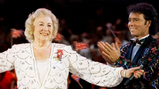 Dame Vera Lynn receives the applause from the audience and fellow performer Cliff Richard during a concert in Hyde Park in London, Britain May 6, 1995