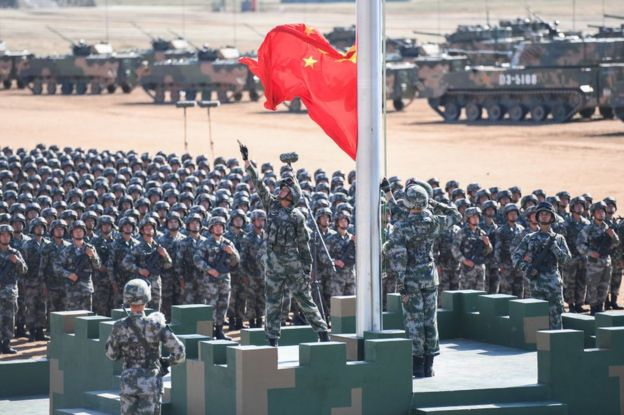 The Chinese flag is raised during a military parade at the Zhurihe training base in China's northern Inner Mongolia region on 30 July 2017