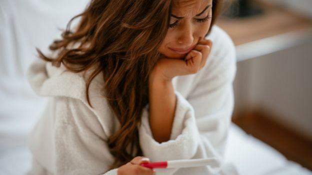 Una mujer mira preocupada una prueba de embarazo.