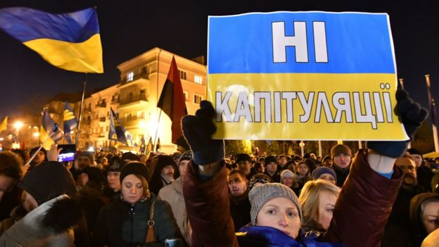 """A woman holds a sign at a protest in Kyiv reading """"no capitulation"""" in Ukrainian"""