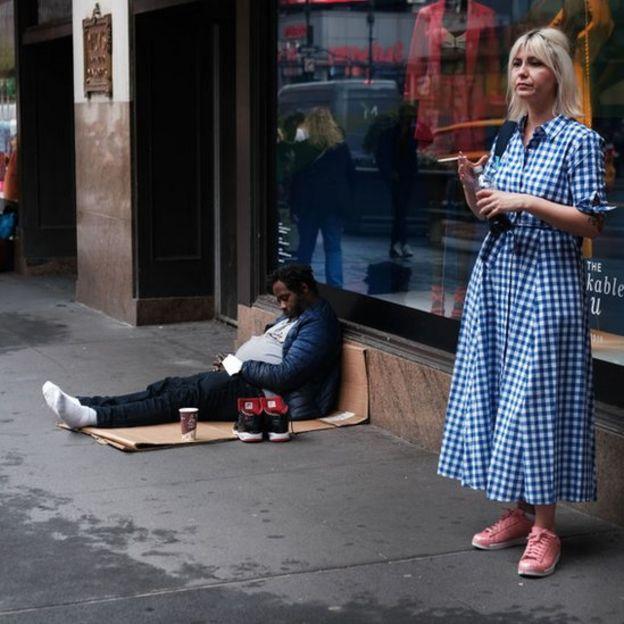 Mulher ao lado de morador de rua pedindo esmola