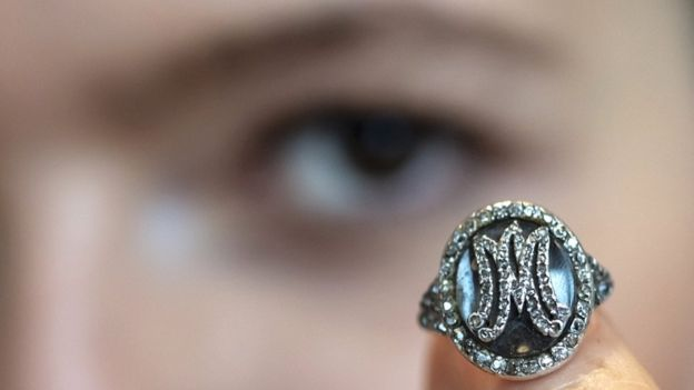 A Sotheby's employee displays a diamond ring bearing the initials MA for Marie Antoinette and containing a lock of her hair during a preview at the Sotheby's in Geneva, Switzerland, on 7 November 2018