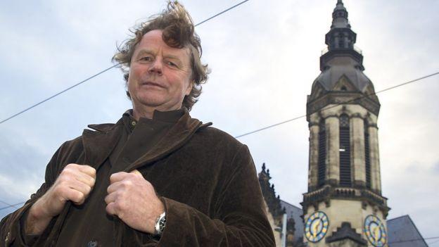 施福克2014年资料照片。背景中的教堂塔楼,他当年就在这里拍摄示威游行的情景