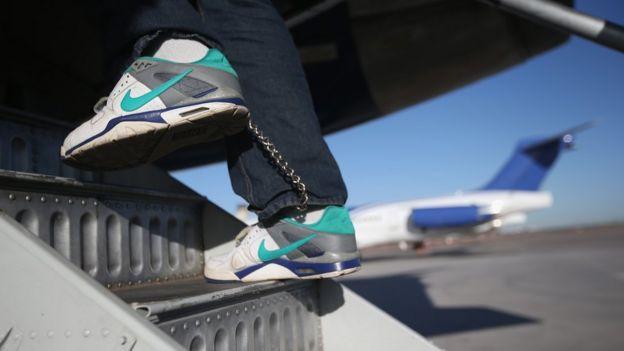 Imigrante subindo em avião para ser deportado