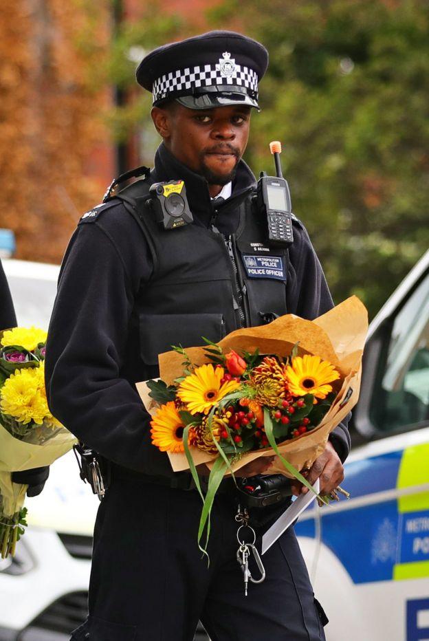 Officer holding flowers