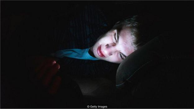 Menino no escuro com celular