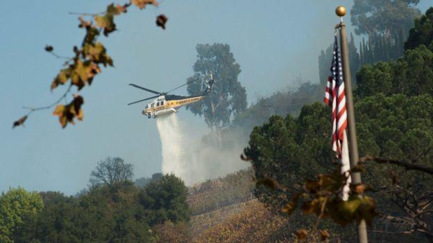 Helicóptero despeja água sobre incêndio