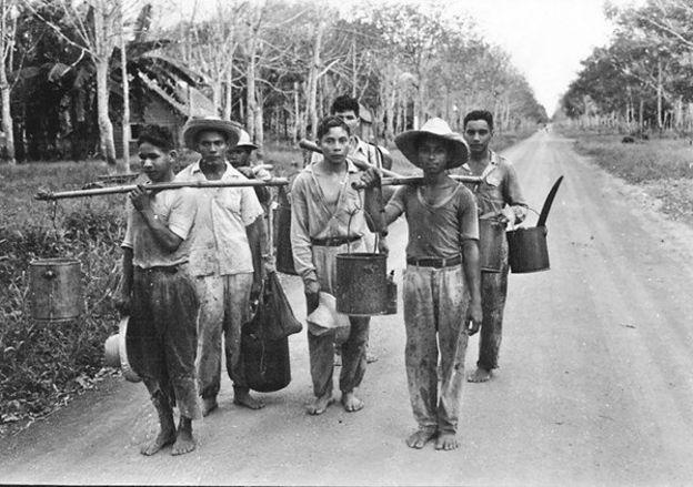 Foto histórica de seringueiros em uma estrada de terra batida na Amazônia paraense
