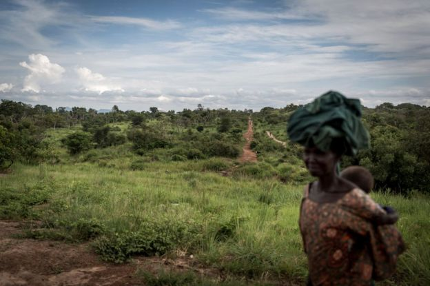A woman, whose face is blurred, carries an infant on her back as she walks from South Sudan into Uganda.