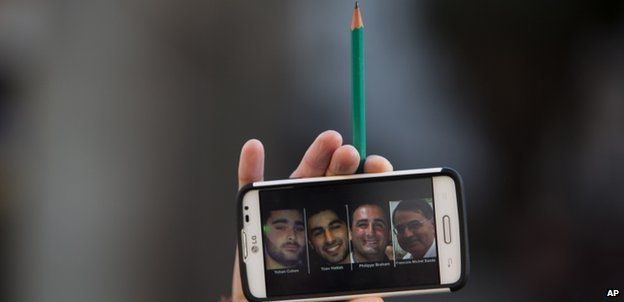 A woman in Tel Aviv holds up a pencil and a mobile phone with a picture of the four Jewish victims