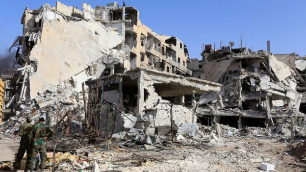 Syrian government forces stand in front of destroyed buildings in the Hajar al-Aswad district of Damascus (21 May 2018)
