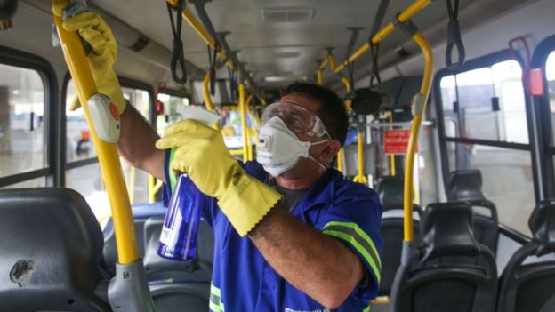Un señor limpia las barandas de un autobús en Brasil