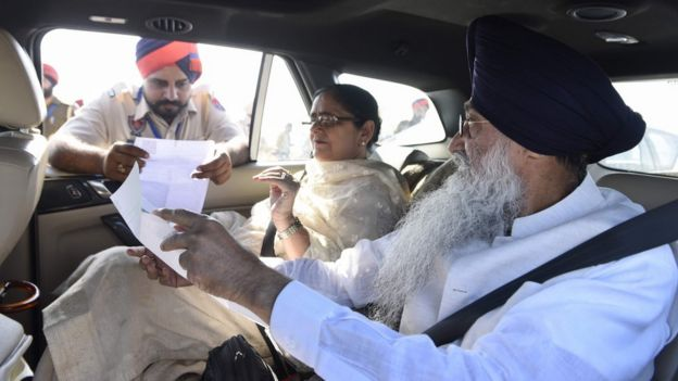 Indian Sikhs show papers to Indian border guards before crossing to Pakistan