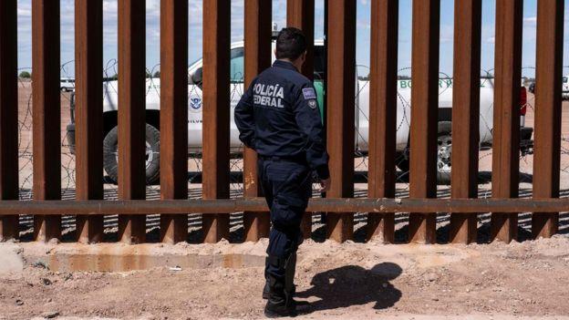 Un policía federal de México observa a través de la barrera fronteriza a una patrulla fronteriza de EE.UU.