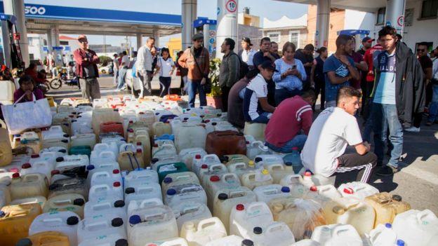 Galones acumulados en el piso, al lado de personas que esperan conseguir gasolina.