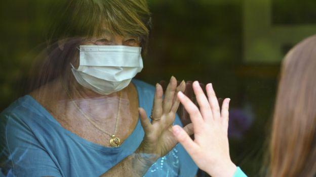 Abuela saludando a su nieta detrás de una ventana
