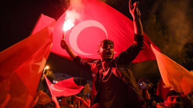 seguidores de Erdogan enrolados em bandeiras da Turquia