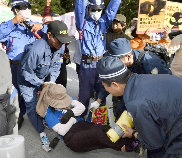 La policía retira a un manifestante de la calle en Japón.