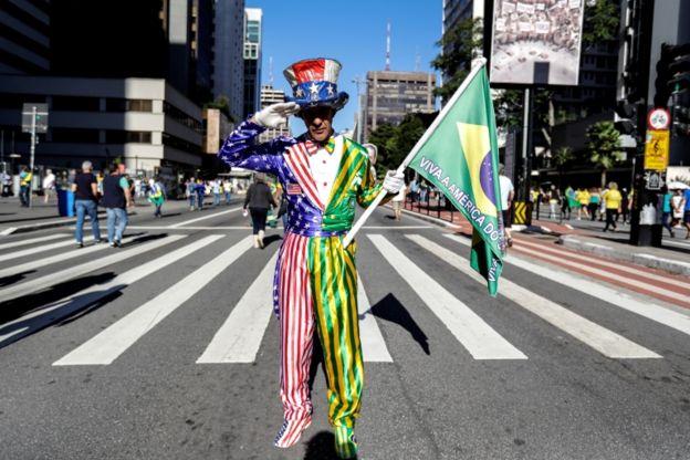 Manifestante na Avenida Paulista, vestindo um traje com uma mescla dos símbolos do Brasil e dos Estados Unidos