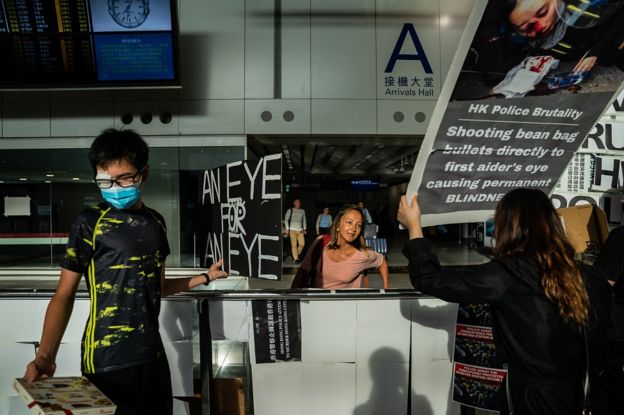 香港國際機場一號客運大樓抵港大堂內兩名示威者舉起抗議標語與旅客交談(13/8/2019)