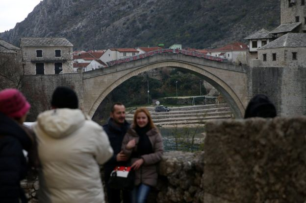 People take pictures in front of Mostar's Old Bridge