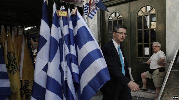 Man walks past stall selling Greek flags