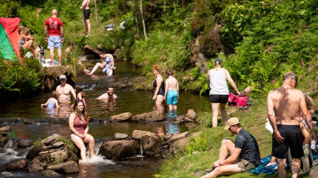 People enjoy the hot weather by Three Shires Head on the River Dane, where Cheshire, Derbyshire and Staffordshire meet