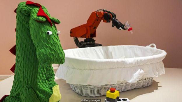 Robô que dá mamadeira e fantasia de dragão