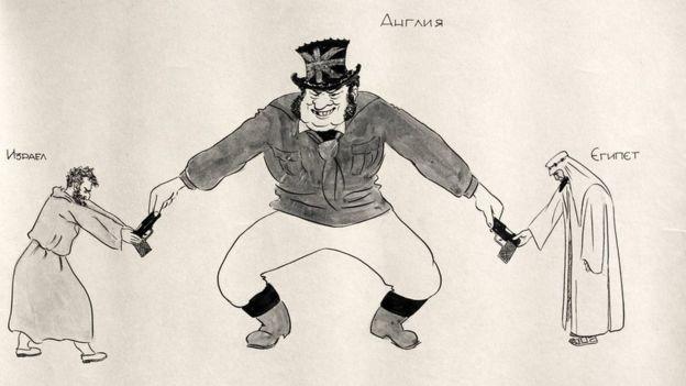 """رسم كاريكاتير من عام 1952 يظهر شخصية """"جون بول"""" الكرتونية التي تمثل بريطانيا يناول فلسطينيا يهوديا وعربيا مسلما على جانبيه سلاحين ناريين( حسب getty)"""