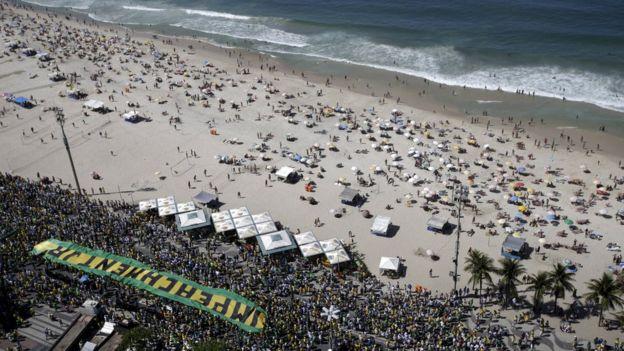 Foto aérea mostra manifestantes e faixa escrita 'Impeachment já' em beira de praia do Rio de Janeiro