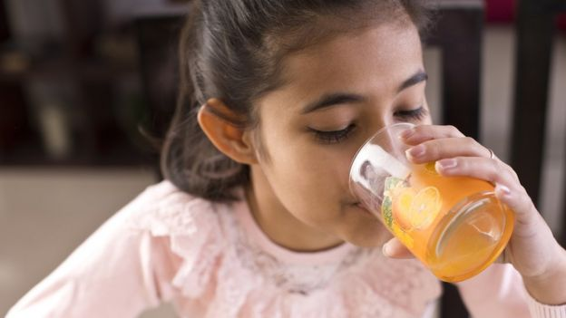 Un niño bebiendo jugo.