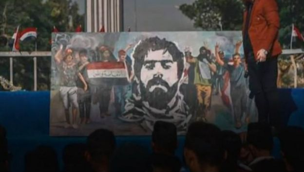A banner, depicting Safaa Al-Saray's face and other young people protesting, at Baghdad's Tahrir Square