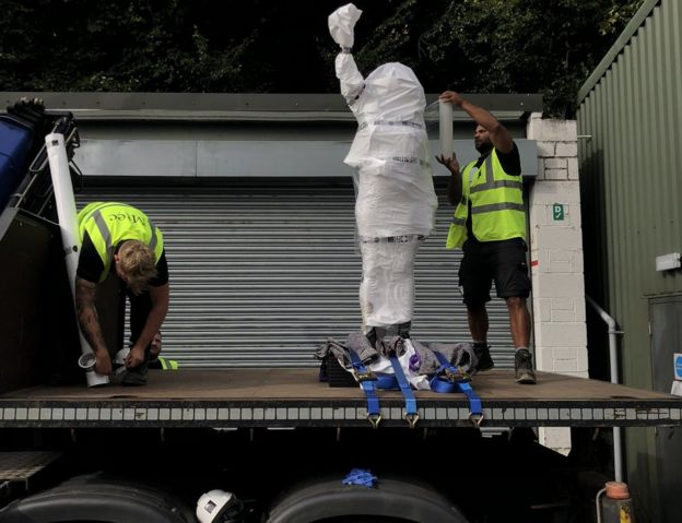 Two men unloading the new statue from a lorry